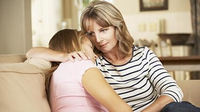 Mother Comforting Teenage Daughter Sitting On Sofa At Home Hugging
